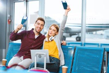 happy girlfriend holding passport above head near smiling boyfriend in airport near luggage