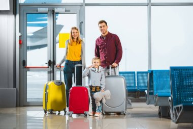 Cheerful family standing with luggage in waiting hall of airport stock vector