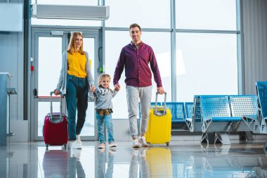 Cheerful husband and wife holding hands with cute daughter and standing with suitcases stock vector
