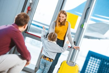 Selective focus kid meeting mother with luggage in airport stock vector