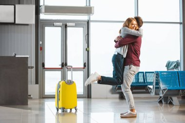 attractive woman hugging boyfriend in waiting hall near suitcase