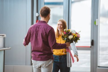 back view of man meeting cheerful girlfriend with bouquet in airport