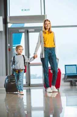 attractive mother holding hands with cute daughter while walking with suitcases in airport