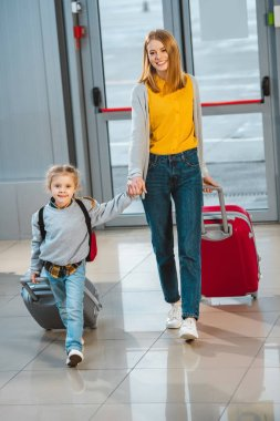 attractive mother holding hands with cute daughter and walking with baggage in airport
