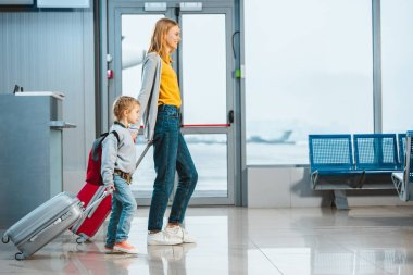 mother and daughter holding hands and walking with baggage in airport