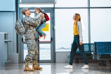 happy father in military uniform holding in arms cute daughter near wife in airport