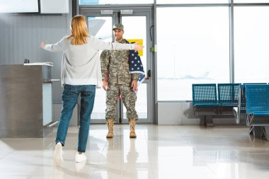 happy girlfriend with opened arms meeting boyfriend in military uniform with american flag in airport