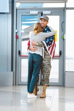 cheerful veteran in military uniform hugging girlfriend in airport