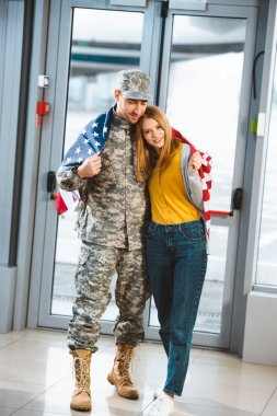 happy veteran in military uniform standing with girlfriend and holding american flag in airport