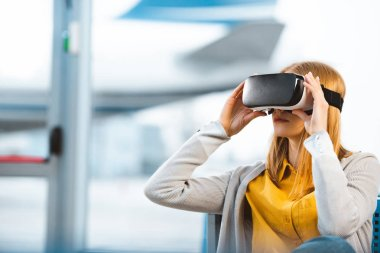 woman wearing virtual reality headset while sitting in departure lounge