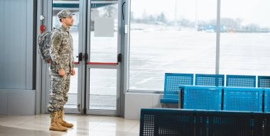 veteran in military uniform standing with backpack in departure lounge