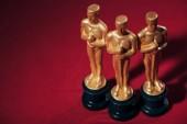 Selektivní fokus zlaté sošky oscar ocenění na červeném pozadí s kopií prostor