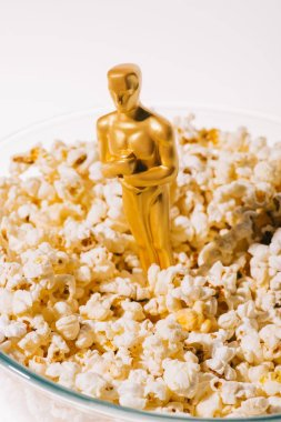 Selective focus of shiny oscar award in popcorn bowl isolated on white stock vector