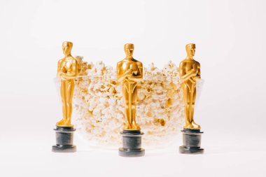 oscar award statuettes with bowl of popcorn isolated on white