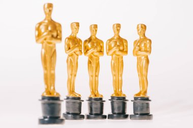 Selective focus of hollywood oscar award statuettes isolated on white stock vector