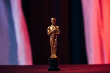 Selective focus of golden oscar award on dark background stock vector