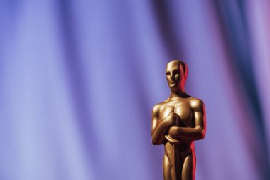 golden oscar award on purple background with copy space