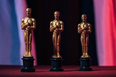 Shiny golden oscar award statuettes on black background stock vector