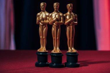Selective focus of golden oscar awards on black background stock vector