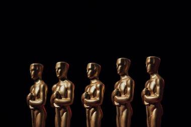 Row of hollywood oscar award statuettes isolated on black stock vector