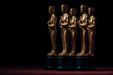 Row of golden oscar award statuettes on black background with copy space stock vector