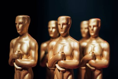 Selective focus of hollywood oscar award statuettes isolated on black stock vector
