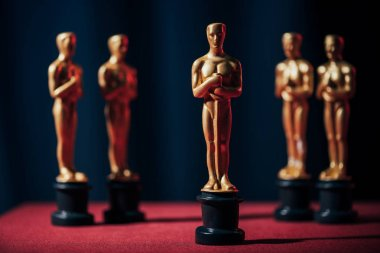 row of hollywood golden oscar awards on dark background