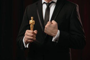 partial view of man in suit with clenched fist holding oscar award on dark background