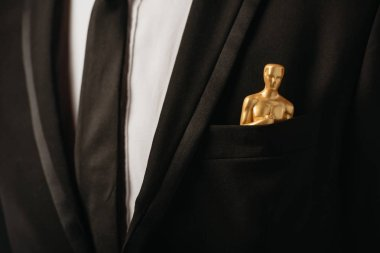 cropped view of man in suit with oscar award in pocket isolated on black