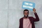 Fotografie smiling african american casual businessman looking at camera and holding speech bubble with time for questions lettering on grey background