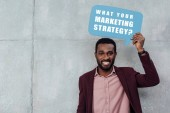 Fotografie smiling african american casual businessman looking at camera and holding speech bubble with what your marketing strategy? lettering on grey background