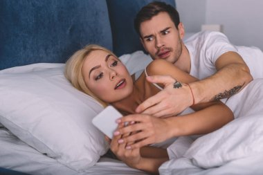 angry man looking at suspicious girlfriend using smartphone in bed, mistrust concept