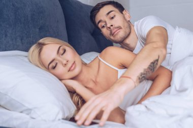 suspicious young man reaching for smartphone while beautiful girlfriend sleeping in bed, mistrust concept
