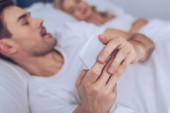 Detailní pohled mladého muže pomocí smartphone, zatímco ležel spící manželku v posteli
