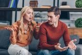 emotivo coppia arrabbiata che si siede sul divano e che litigano su smartphone, diffidenza di concetto