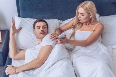 high angle view of shocked young woman showing smartphone to confused boyfriend lying in bed