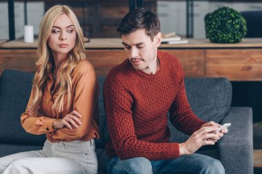 unhappy young woman sitting with crossed arms and looking at husband with smartphone, distrust concept