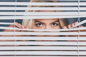 young woman looking at camera and peeking through blinds