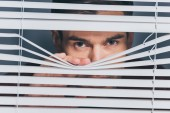 suspicious young man looking at camera through blinds, mistrust concept