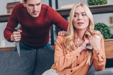 aggressive man with knife looking at girlfriend using smartphone at home, mistrust concept