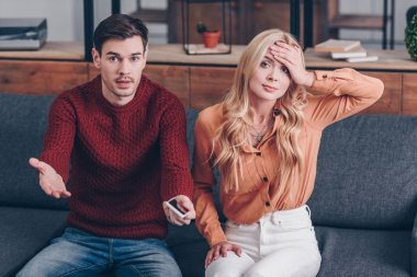 jealous man with smartphone and upset woman sitting on couch and looking at camera, distrust concept