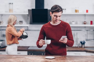 young man holding cup and using smartphone in kitchen, relationship problem concept