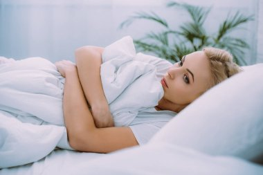 selective focus of upset woman holding blanket while lying in bed at home