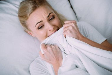 frightened woman lying in bed, crying and holding blanket