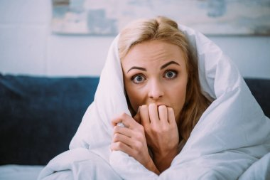 scared woman covered in blanket biting hand and looking at camera in bed