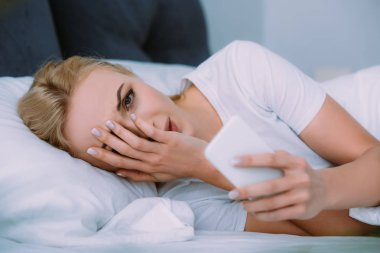 stressed woman lying in bed, looking at camera, covering face with hand and using smartphone