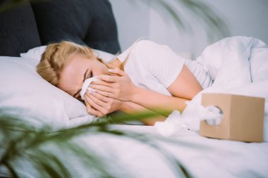 selective focus of woman wiping tears and crying while lying in bed at home