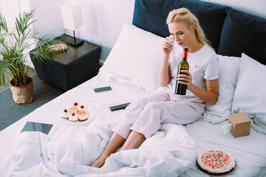 upset woman with bottle of wine wiping tears while celebrating birthday in bed alone