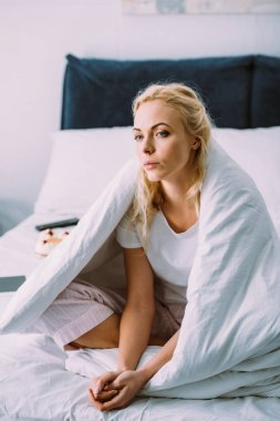 selective focus of sad lonely woman covered in blanket sitting on bed at home