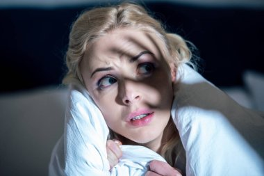 selective focus of frightened woman covered in white blanket looking away
